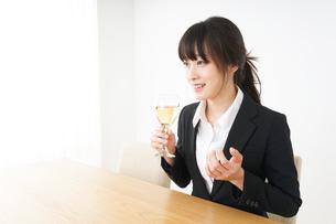 スーツ姿でお酒を飲む若い女性の写真素材 [FYI04656476]