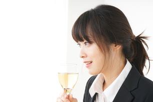 スーツ姿でお酒を飲む若い女性の写真素材 [FYI04656483]