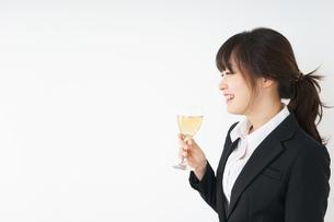 スーツ姿でお酒を飲む若い女性の写真素材 [FYI04656484]
