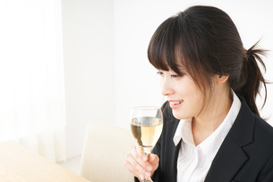スーツ姿でお酒を飲む若い女性の写真素材 [FYI04656485]