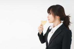 スーツ姿でお酒を飲む若い女性の写真素材 [FYI04656487]