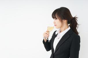 スーツ姿でお酒を飲む若い女性の写真素材 [FYI04656488]