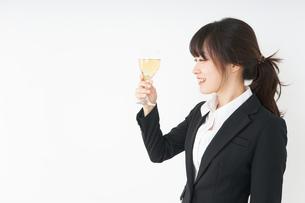 スーツ姿でお酒を飲む若い女性の写真素材 [FYI04656502]