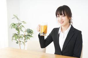スーツでビールを飲むビジネスウーマンの写真素材 [FYI04656660]