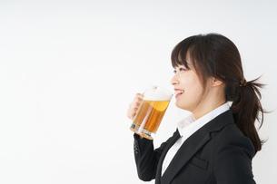 スーツでビールを飲むビジネスウーマンの写真素材 [FYI04656661]