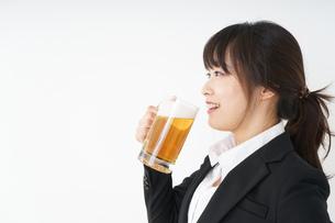 スーツでビールを飲むビジネスウーマンの写真素材 [FYI04656662]