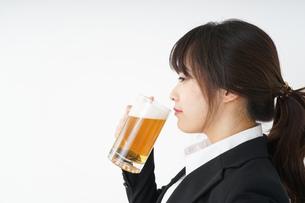 スーツでビールを飲むビジネスウーマンの写真素材 [FYI04656665]