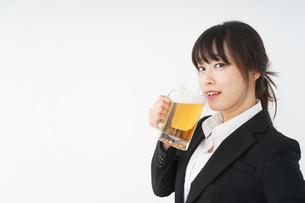 スーツでビールを飲むビジネスウーマンの写真素材 [FYI04656666]