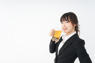 スーツでビールを飲むビジネスウーマンの写真素材 [FYI04656667]