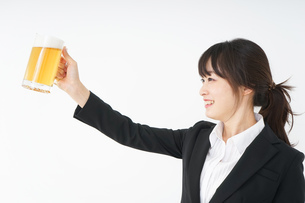 スーツでビールを飲むビジネスウーマンの写真素材 [FYI04656668]