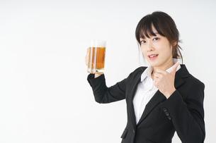 スーツでビールを飲むビジネスウーマンの写真素材 [FYI04656669]
