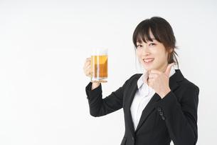 スーツでビールを飲むビジネスウーマンの写真素材 [FYI04656670]