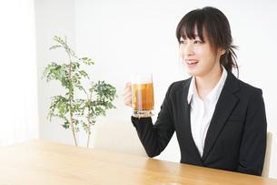 スーツでビールを飲むビジネスウーマンの写真素材 [FYI04656672]