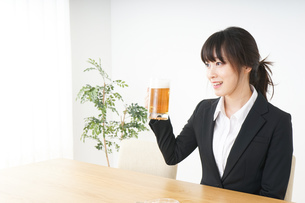 スーツでビールを飲むビジネスウーマンの写真素材 [FYI04656673]