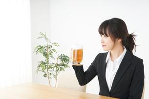 スーツでビールを飲むビジネスウーマンの写真素材 [FYI04656674]