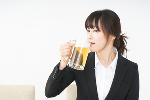 スーツでビールを飲むビジネスウーマンの写真素材 [FYI04656676]
