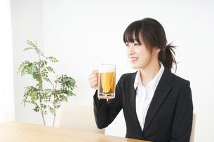 スーツでビールを飲むビジネスウーマンの写真素材 [FYI04656677]