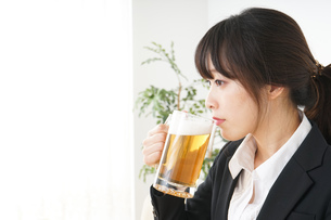 スーツでビールを飲むビジネスウーマンの写真素材 [FYI04656678]
