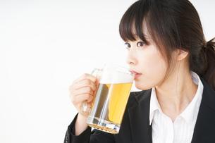 スーツでビールを飲むビジネスウーマンの写真素材 [FYI04656679]
