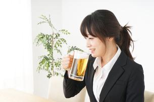 スーツでビールを飲むビジネスウーマンの写真素材 [FYI04656680]