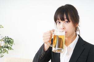 スーツでビールを飲むビジネスウーマンの写真素材 [FYI04656681]