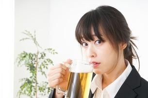 スーツでビールを飲むビジネスウーマンの写真素材 [FYI04656682]