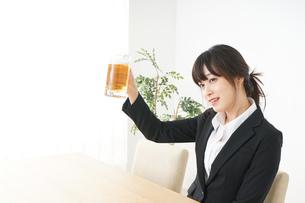 スーツでビールを飲むビジネスウーマンの写真素材 [FYI04656684]