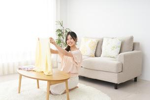 洗濯物をたたむ若い女性の写真素材 [FYI04656893]