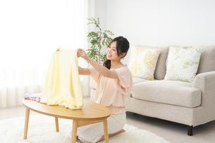 洗濯物をたたむ若い女性の写真素材 [FYI04656894]
