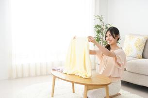 洗濯物をたたむ若い女性の写真素材 [FYI04656895]