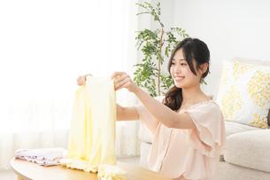 洗濯物をたたむ若い女性の写真素材 [FYI04656897]