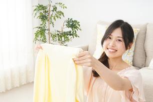 洗濯物をたたむ若い女性の写真素材 [FYI04656898]