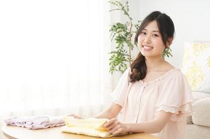 洗濯物をたたむ若い女性の写真素材 [FYI04656900]