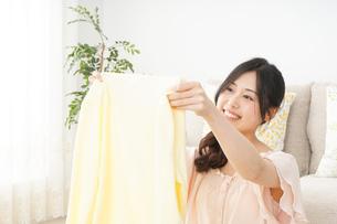 洗濯物をたたむ若い女性の写真素材 [FYI04656901]