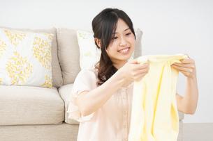 洗濯物をたたむ若い女性の写真素材 [FYI04656902]