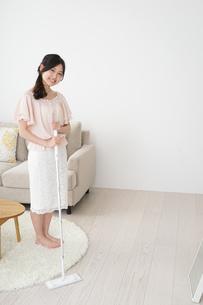 自宅を掃除する若い女性の写真素材 [FYI04656907]