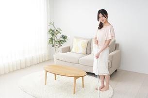 自宅を掃除する若い女性の写真素材 [FYI04656908]