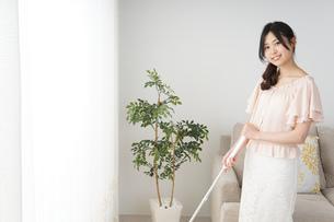 自宅を掃除する若い女性の写真素材 [FYI04656911]