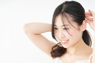 髪の毛をセットする若い女性の写真素材 [FYI04656926]