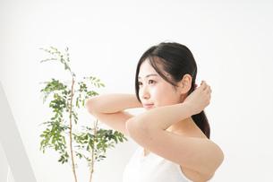 髪の毛をセットする若い女性の写真素材 [FYI04656927]