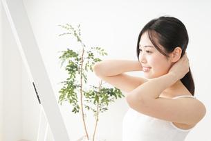 髪の毛をセットする若い女性の写真素材 [FYI04656928]