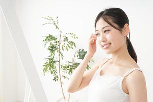 髪の毛をセットする若い女性の写真素材 [FYI04656929]