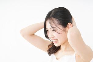 髪の毛をセットする若い女性の写真素材 [FYI04656932]