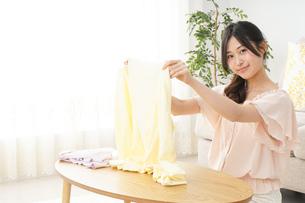 洗濯物をたたむ若い女性の写真素材 [FYI04656946]