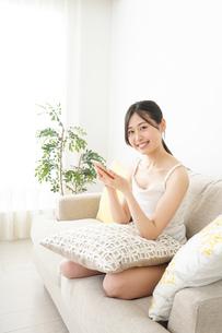部屋でスマホを使う若い女性の写真素材 [FYI04656998]