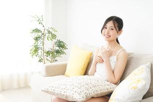 部屋でスマホを使う若い女性の写真素材 [FYI04656999]