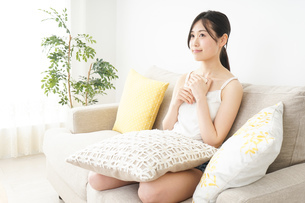 部屋でスマホを使う若い女性の写真素材 [FYI04657000]