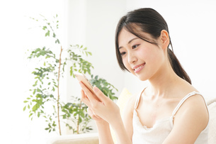 部屋でスマホを使う若い女性の写真素材 [FYI04657006]