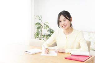 自宅で勉強をする若い女性の写真素材 [FYI04657093]