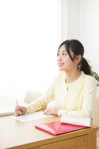 自宅で勉強をする若い女性の写真素材 [FYI04657094]